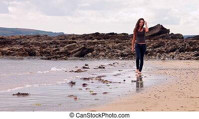 Pretty brunette walking along the water