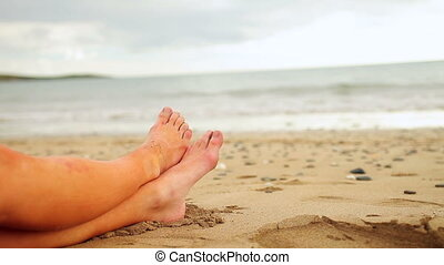 Womans legs sitting on the beach by the water on a cloudy...
