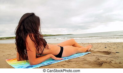 Fit brunette lying on the beach on a towel on a cloudy day