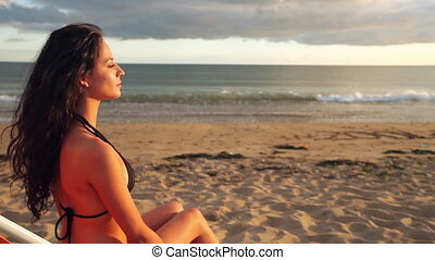 Calm brunette sitting on a deck chair relaxing at the beach