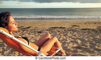 Peaceful brunette sitting on a deck chair