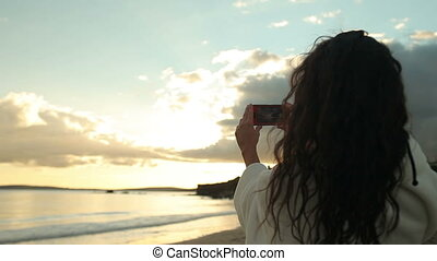 Brunette woman taking a photo of the sunset on her...
