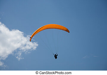 Paraglider - A Paraglider flies in the blue sky.