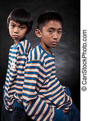 Cousins - Two young eleven year old asian boys standing with...
