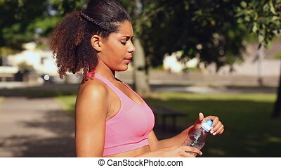 sporty woman drinking water standing on the street