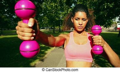 Slender woman using dumbbells in park