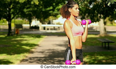 Content sporty woman lifting dumbbells in park