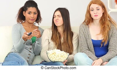 Three friends watching television in living room