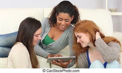 Woman showing her tablet to her friends in living room