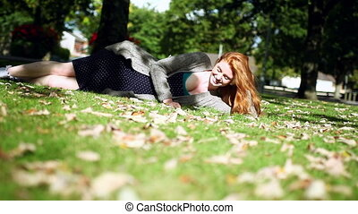 Cheerful redhead relaxing lying on green lawn in bright...