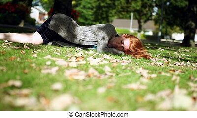 Peaceful napping redhead lying on grass - Peaceful napping...