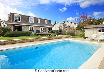 Large backyard with flowerbed and swimming pool
