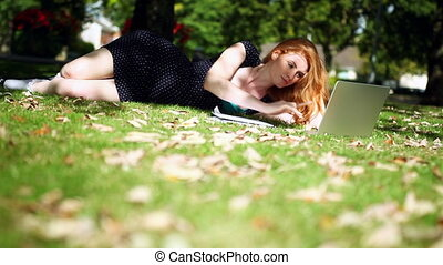 Lovely redhead using her notebook for doing assignments...