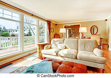 Floor-to-ceiling windows living room with a rustic beige couch