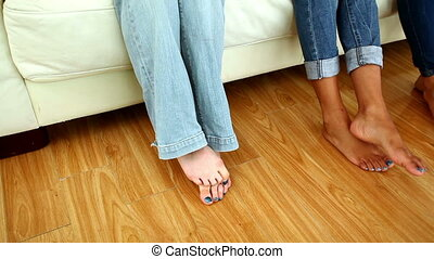 Young barefooted friends sitting on couch in bright living...