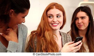 Cute female friends using smartphone
