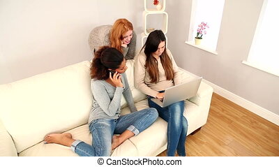 Content women sitting on couch using their smartphones and a...