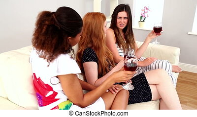 Beautiful young women sitting on couch holding wine glasses...
