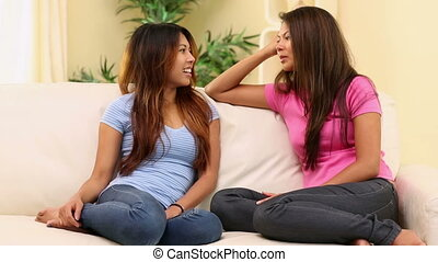 Two attractive happy sisters sitting on couch chatting in...