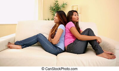Two pretty sisters sitting on couch arguing in bright living...