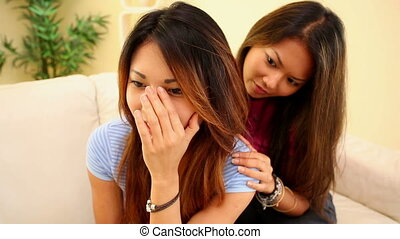 Girl comforting sister on couch in bright living room