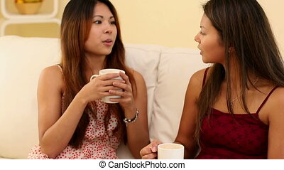 Attractive sisters sitting on couch holding cups in bright...