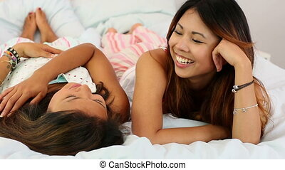 Pretty sisters lying on bed chatting in bright bedroom