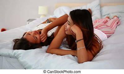 Sisters in pajamas lying on bed chatting