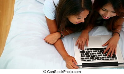 Beautiful happy sisters lying on bed using laptop in bright...