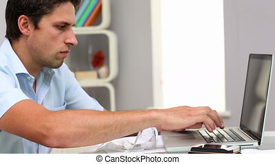Focused attractive man working with his notebook in living...
