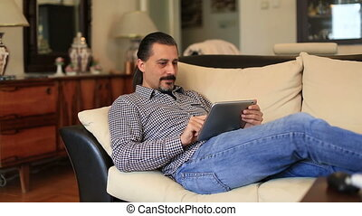 attractive handsome lieying sofa and using tablet computer...