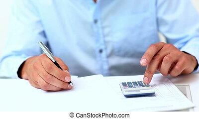 Closeup of young businessman calculating