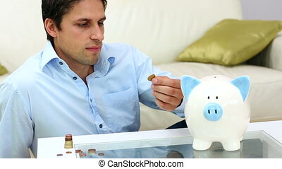 Cute young man putting money into a piggy bank in bright...