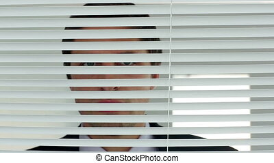 Calm businessman peering out of his window standing in his...