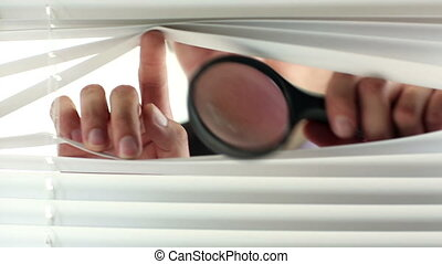 Curious businessman peering out of his office using a...