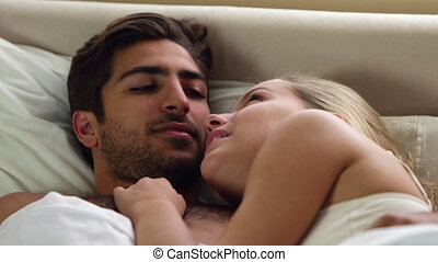 Couple lying in bed and chatting at home in bedroom