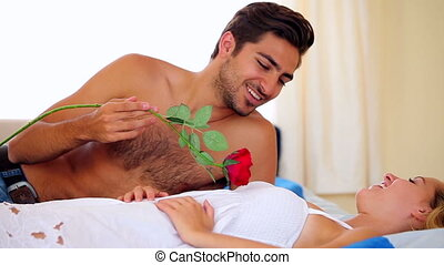 Man tickling his girlfriend with a red rose on bed at home...
