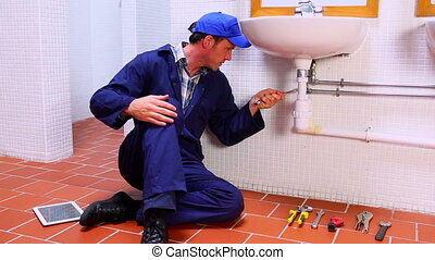 Handsome plumber fixing sink and checking tablet pc in a...