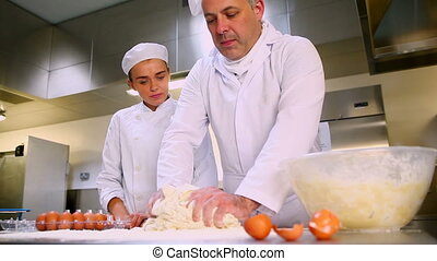 Head chef showing trainee how to prepare dough in a...