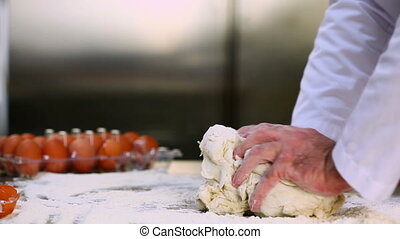 Chefs hands kneading out dough in a commercial kitchen