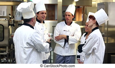 Team of chefs chatting together in a commercial kitchen