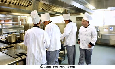 Head chef supervising his team then smiling at camera in a...