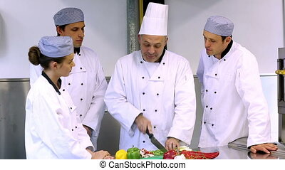 Head chef showing his trainees how to slice vegetables in a...