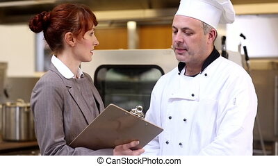 Restaurant manager chatting with head chef in a commercial...