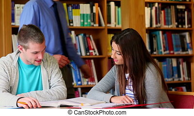 Smiling lecturer helping his students in the library at the...