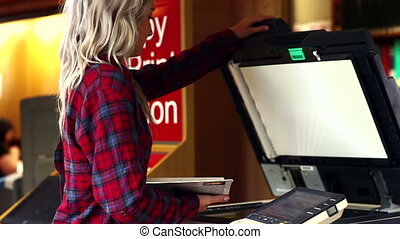 Blonde student using the photocopier in the library at the...