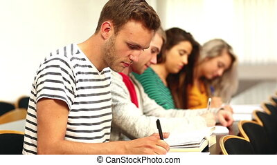 Focused students taking notes in class in college