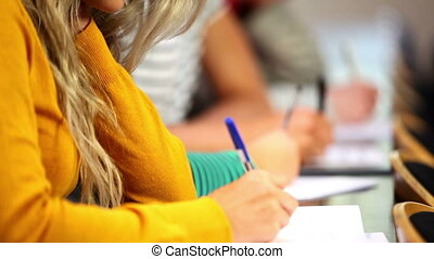 Row of students taking notes in classroom in college