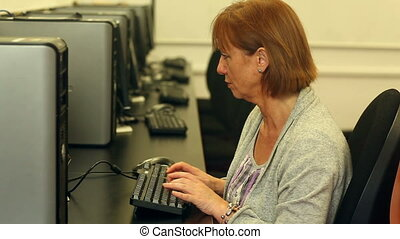 Mature student working with a computer sitting in computer...