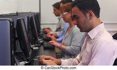 Class of mature students working in computer class at the...